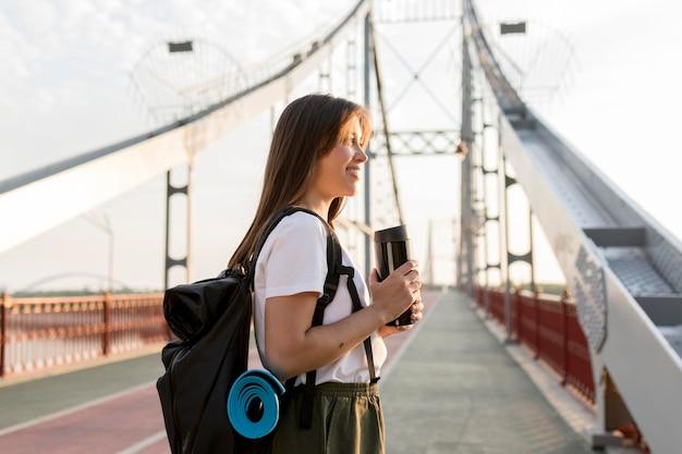 Seitenansicht der glücklichen reisenden frau mit rucksack auf brücke, die thermoskanne hält