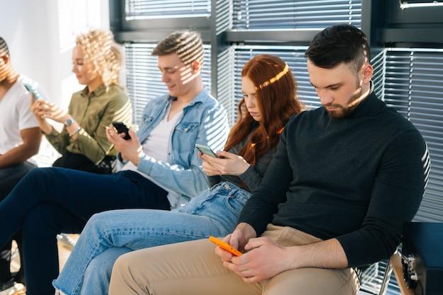 Seitenansicht der gruppe fünf junger kandidaten unterschiedlicher ethnischer herkunft, die mobiltelefone verwenden, während sie auf ein vorstellungsgespräch in der modernen bürolobby warten. multiethnische menschen für eine freie stelle, die auf stühlen im warteschlangenkorridor sitzen.