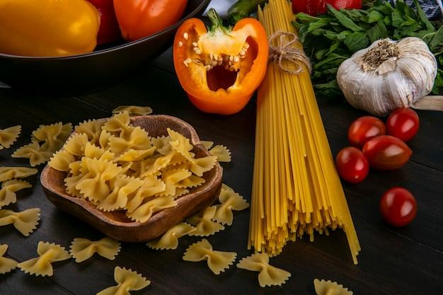 Seitenansicht der hälften der mehrfarbigen paprika mit rohen spaghetti und nudelknoblauch und tomaten auf einer holzoberfläche