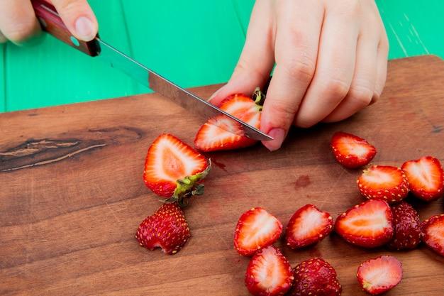 Seitenansicht der hände, die erdbeeren mit messer auf schneidebrett auf grüner oberfläche schneiden