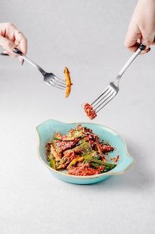 Seitenansicht der hände halten gabeln über dem teller mit avocadosalat mit fleisch und sesam