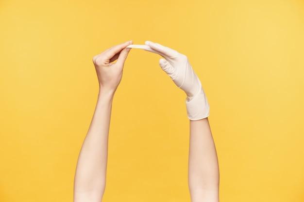 Seitenansicht der hand der jungen frau, die gummihandschuh von der anderen hand herauszieht, während über orange hintergrund isoliert wird. menschliche hände und gestik