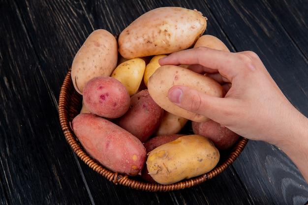 Seitenansicht der hand, die kartoffel mit korb voller kartoffeln auf holztisch hält