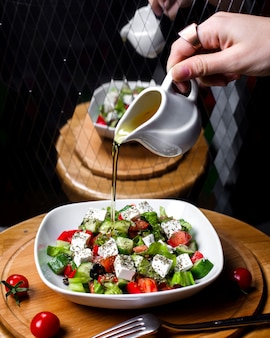 Seitenansicht der hand, die olivenöl auf frischem salat mit feta-käse-tomatengurken in weißer schüssel gießt