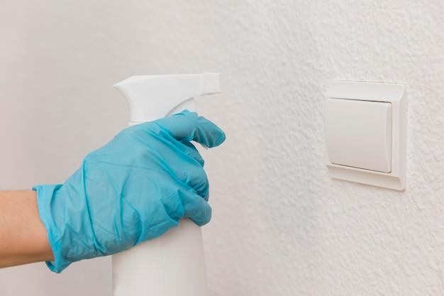 Seitenansicht der hand mit chirurgischem handschuh, der desinfektionsmittel auf lichtschalter sprüht