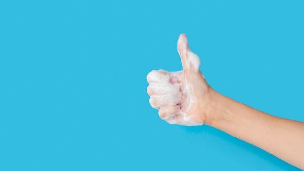 Seitenansicht der hand mit schaum aus seife und daumen nach oben