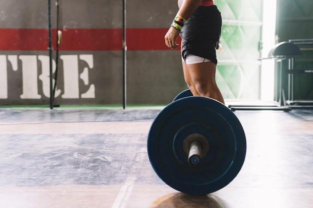 Seitenansicht der hantel und mann im fitnessstudio