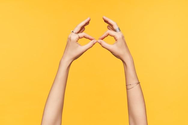 Seitenansicht der hellhäutigen hände der jungen frau, die über gelbem hintergrund lokalisiert wird, während mit gefalteten fingerbrillen nachgeahmt wird. konzept der hände und körpersprache