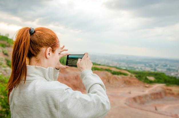 Seitenansicht der ingwerfrau foto auf smartphone machend
