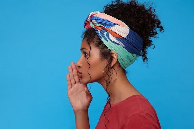 Seitenansicht der jungen attraktiven dunkelhaarigen lockigen frau mit gesammeltem haar, das erhabene handfläche nahe ihrem mund hält, während sie etwas geheimnisvolles erzählt, isoliert über blauer wand