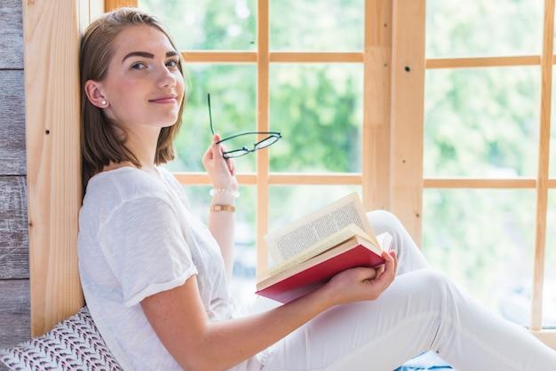 Seitenansicht der jungen frau brillen und buch halten nahe dem fenster