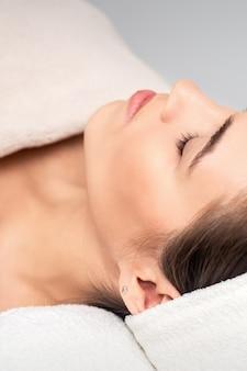 Seitenansicht der jungen frau, die auf kosmetiktisch mit geschlossenen augen liegt, während auf kosmetische prozedur im schönheitssalon wartet