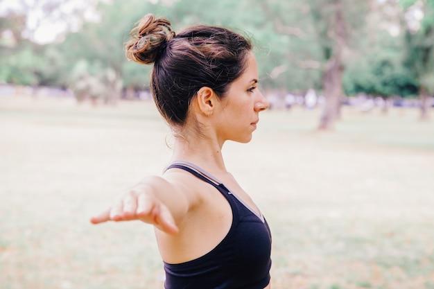 Seitenansicht der jungen frau, die friedlich yoga draußen praktiziert. pilates gesunder lebensstil für menschen in yoga-tradition. training im freien konzept. menschen, die wohlfühlmeditation im park machen.