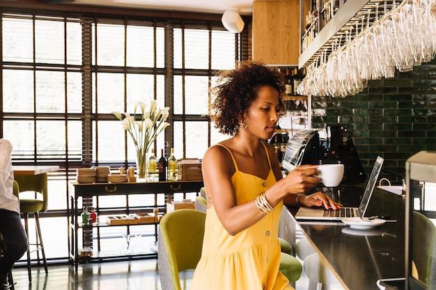 Seitenansicht der jungen frau mit dem gelockten haar, das kaffeetasse unter verwendung des laptops am barzähler hält