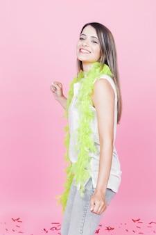 Seitenansicht der jungen frau mit grüner boa um ihr stutzentanzen