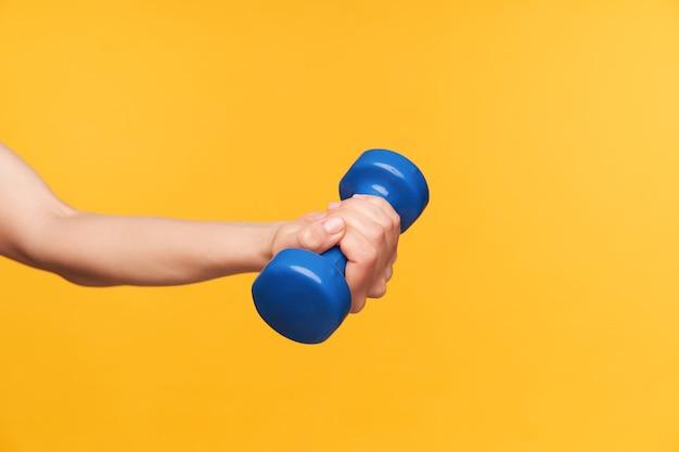 Seitenansicht der jungen hellhäutigen frauenhand mit der nackten maniküre, die blaue hantel in ihr hält, während fitnessklasse, lokalisiert über gelbem hintergrund