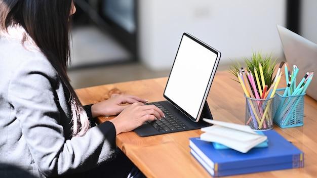 Seitenansicht der jungen kreativen designerin, die mit tablet-computer am schreibtisch aus holz arbeitet.