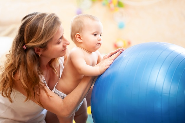 Seitenansicht der jungen mutter, die dem kleinen baby hilft, windeln zu tragen, die gymnastikübungen üben