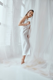 Seitenansicht der jungen schönen brünetten frau, die lilieblume steht und hält. porträt des mädchens im weißen seidenkleid mit nassem haar, das auf weißem hintergrund zwischen tüll aufwirft. konzept der schönheit.