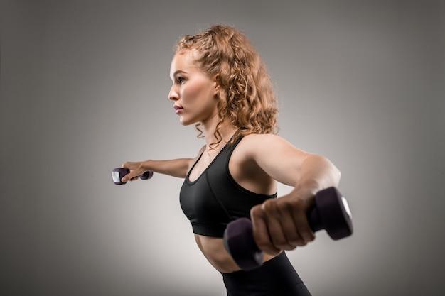 Seitenansicht der jungen sportlerin im schwarzen trainingsanzug, der hanteln anhebt und während der körperlichen übung auf grau atmet