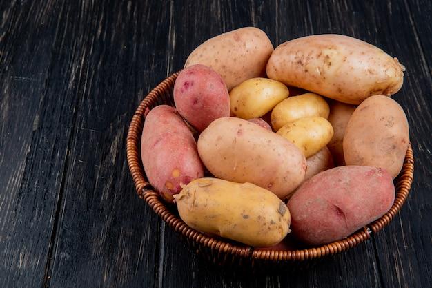 Seitenansicht der kartoffeln im korb auf holztisch mit kopienraum