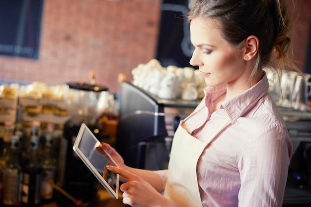 Seitenansicht der kellnerin mit digitalem tablet