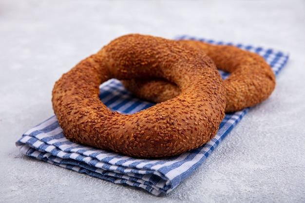 Seitenansicht der köstlichen und weichen traditionellen türkischen bagels lokalisiert auf einem karierten tuch auf einem weißen hintergrund