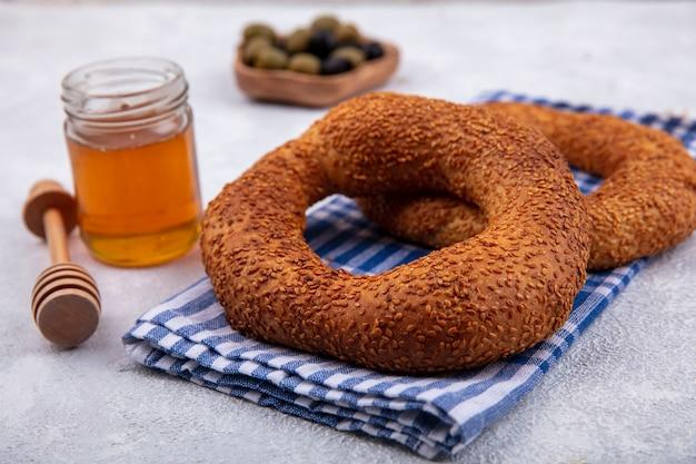 Seitenansicht der köstlichen und weichen traditionellen türkischen bagels lokalisiert auf einem karierten tuch mit honig und honiglöffel auf einem weißen hintergrund