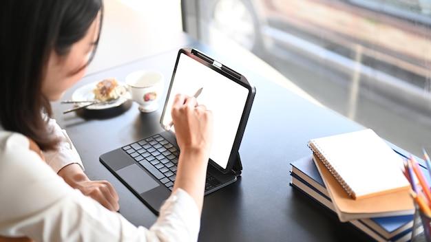 Seitenansicht der kreativen frau, die nahe glasfenster sitzt und im computertablett arbeitet.