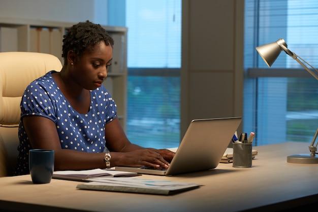 Seitenansicht der kubanischen frau antwortend auf e-mails bei der arbeit am abend