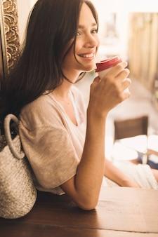 Seitenansicht der lächelnden frau einwegkaffee trinkend