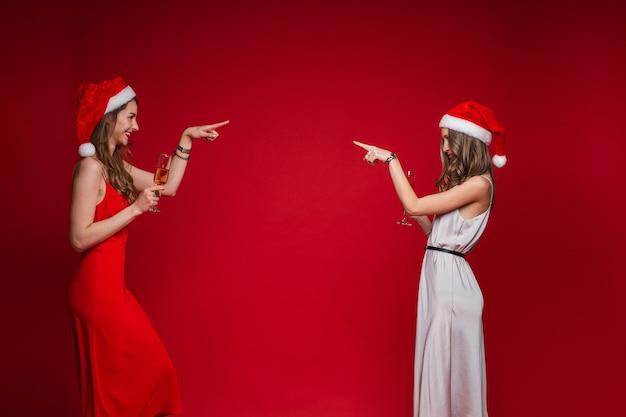 Seitenansicht der lächelnden hübschen jungen frauen in den weihnachtsmützen, die finger auf einander zeigen, lokalisiert auf roter wand
