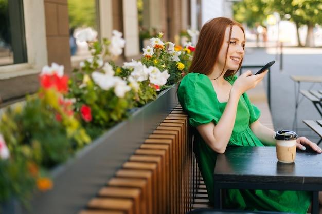 Seitenansicht der lächelnden rothaarigen jungen frau, die audio-sprachnachricht auf dem handy aufnimmt, die am tisch mit kaffeetasse auf der café-terrasse im freien am sonnigen sommertag sitzt.