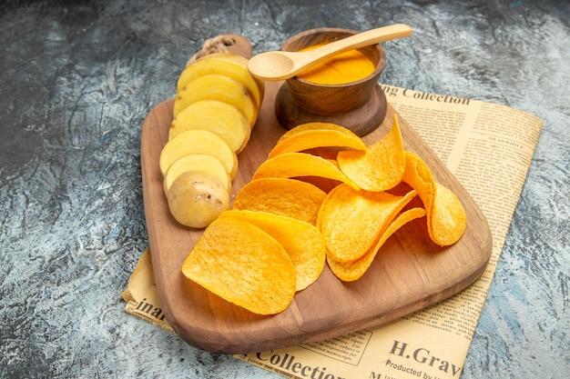 Seitenansicht der leckeren hausgemachten pommes frites schneiden kartoffelscheiben auf holzschneidebrett auf zeitung auf grauem tisch