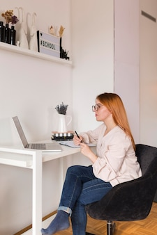 Seitenansicht der lehrerin am schreibtisch während der online-klasse