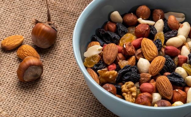 Seitenansicht der mischung von nüssen und getrockneten früchten in einer schüssel auf rustikalem