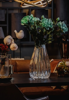 Seitenansicht der modernen geprägten glasvase mit grünen blumen auf einem holztisch