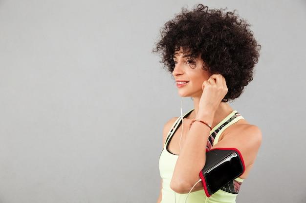 Seitenansicht der musik, die lockige fitnessfrau hört