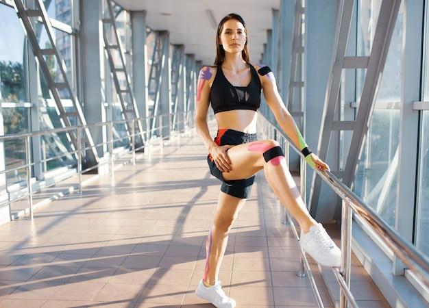 Seitenansicht der muskulösen brünetten frau, die schwarzes sportoutfit trägt