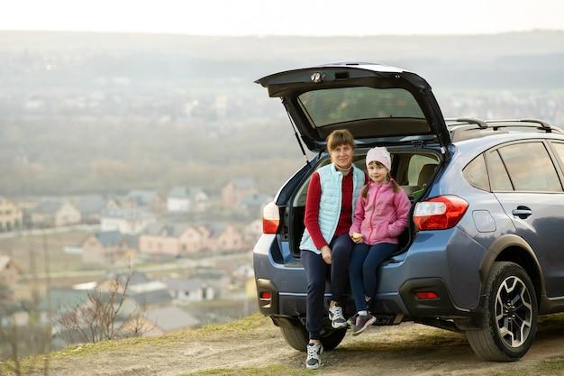 Seitenansicht der mutter mit tochter, die im kofferraum sitzt und auf die natur schaut. konzept des ausruhens mit der familie an der frischen luft.
