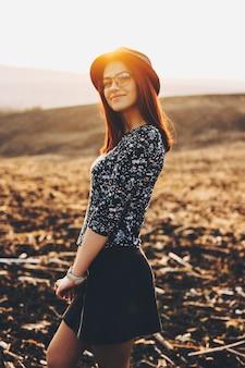 Seitenansicht der niedlichen jungen frau im trendigen outfit lächelnd und kamera betrachtend, während auf hintergrund der herbstwiese während des erstaunlichen sonnenuntergangs stehend. lächelnde dame im feld während des sonnenuntergangs