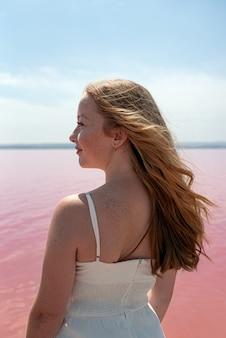 Seitenansicht der niedlichen teenagerfrau, die sommerkleidung trägt, die auf einem erstaunlichen rosa see steht