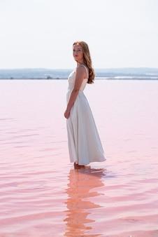 Seitenansicht der niedlichen teenagerfrau, die weißes kleid steht, das auf einem erstaunlichen rosa see steht