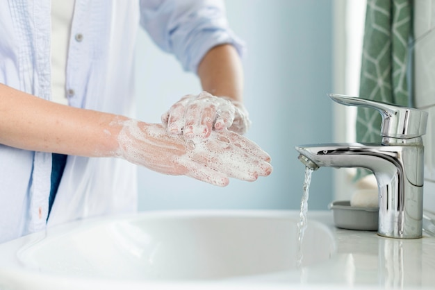 Seitenansicht der person, die hände im badezimmer wäscht
