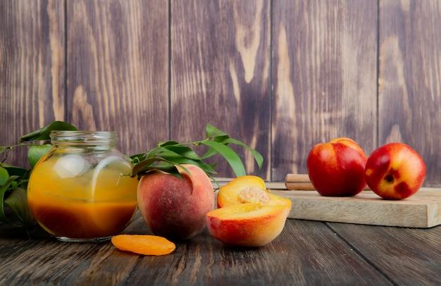 Seitenansicht der pfirsichmarmelade in einem glas und in den frischen reifen pfirsichen auf hölzernem hintergrund