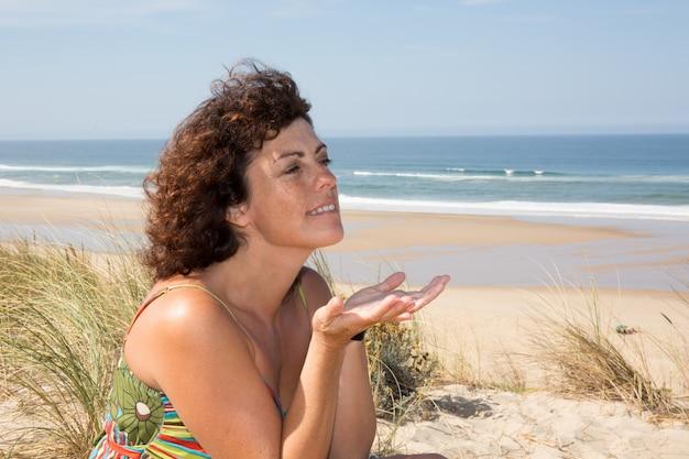 Seitenansicht der ruhigen frau sitzend auf sandigem strand