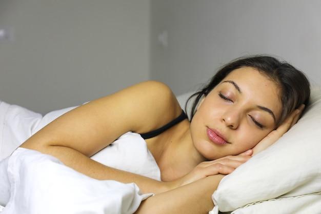 Seitenansicht der schönen jungen frau, die in ihrem bett zu hause schläft