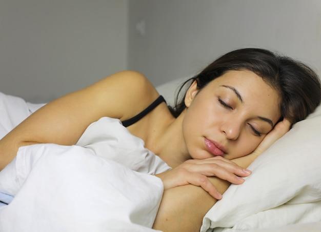 Seitenansicht der schönen jungen frau, die lächelt, während sie in ihrem bett zu hause schläft