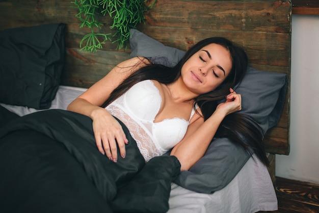 Seitenansicht der schönen jungen frau lächelnd, während sie in ihrem bett zu hause schläft