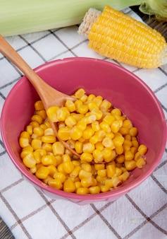 Seitenansicht der schüssel der gelben erbse und des holzlöffels mit geschnittenem mais auf kariertem stoff